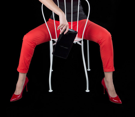 Fashion dressed sexy girl sitting on a chair. On a black background.