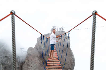 downstream: Man walks on a suspension bridge on the cliffs in the fog.