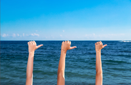 three hands: Three hands indicate the direction of the sea in the background sky of the horizon. Stock Photo