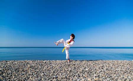 The girl training on the beach: Taekwondo, sports Stock Photo
