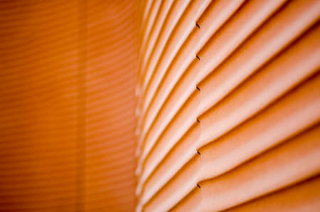 detail of a house with wavy lines, made with red concrete material that recall the silhouettes such as the sand dunes in the desert smoothed by the wind, of the seabed. 写真素材