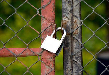 Padlock on an iron bars fence photo