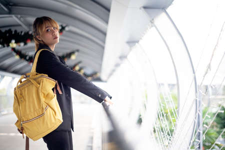 Blond hair woman in black suiit standing on the skywalk with yellow backpack and hang the handrail as a leading line. Reklamní fotografie