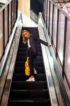 Low angle shot of blond hair woman standing on escalator with yellow backpack, turn back to look with camera.