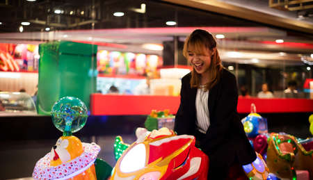 Blond hair woman in black and white clothes enjoy play things at amusement area in shopping mall after meeting with client. Stock Photo