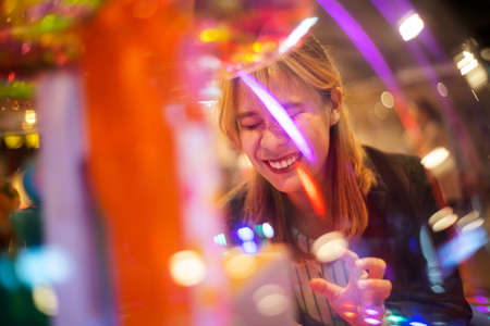 Blond hair woman touch the dome glass of gashapon and smile bigger while she get the item she wants after put the coin. Imagens