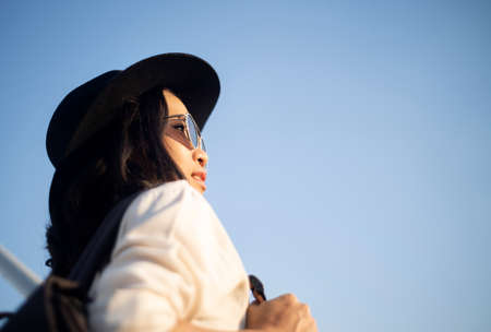 Wavy woman in black hat and sunglasses standing on the rooftop watching the view of sunrise with happiness and gladness.