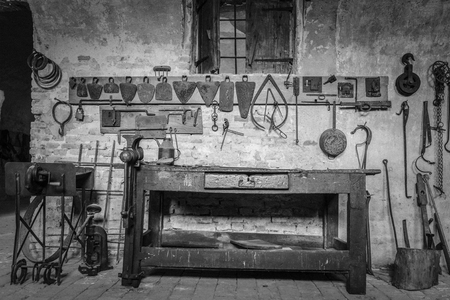 old desk: Old wooden workbench with tools with black and white retrò effect