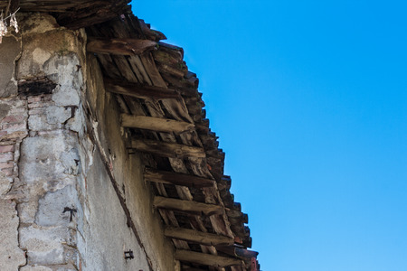damaged roof: damaged roof of an old house, seen from below with blue sky in the background Stock Photo