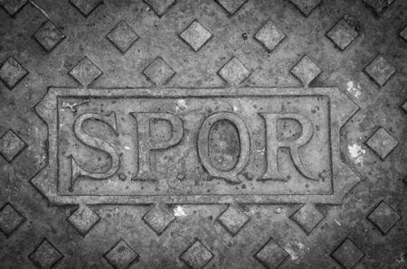 spqr: Una cubierta de boca de desagüe en Roma, Italia, con las letras SPQR.