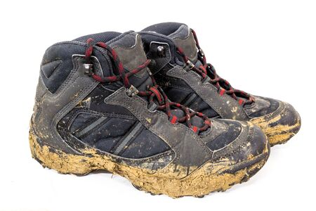 adult footprint: Close-up of muddy shoes after a hike on the mountain.
