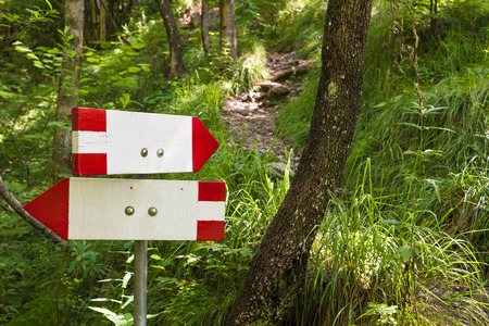 indication: Close up of an isolated signboard along a trekking path. Direction indication. Arrow