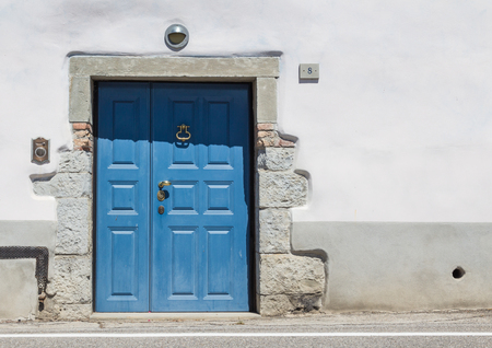front house: Blue wooden front door to the house in Italy Stock Photo