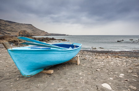 chromatic: boat moored on the beach before the storm
