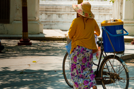 bycicle: Asian Woman with bycicle and hat walking in Myanmar Burma