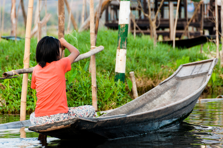 entrapment: Asian girl rowing on boat at Inle Lake Burma Myanmar