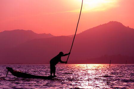 fisherman: Silhouette of fisherman at sunset Inle Lake Burma Myanmar Stock Photo