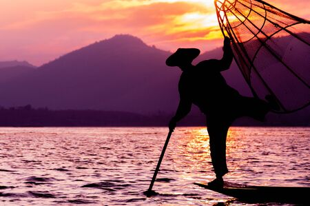 fishing lake: Silhouette of fisherman at sunset Inle Lake Burma Myanmar Stock Photo
