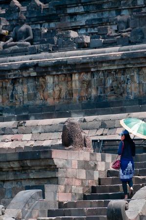 A woman climbing up the brick stairs of a Borobudur hindu temple