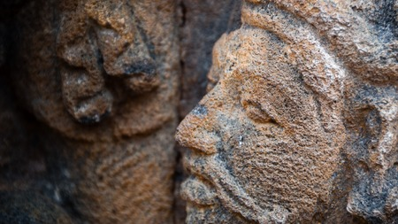 Face carving in stone Sculpture at  biggest Buddhist temple Borobudur temple in Indonesia Stock Photo