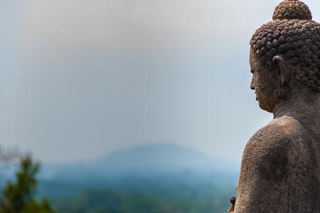 stone buddha: Meditating sitting Buddha in stone above jungle at Borobudur in Java, Indonesia Stock Photo