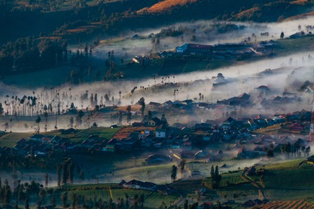 murk: Thin Fog and mist of volcano Bromo surrounding the Field and village Stock Photo