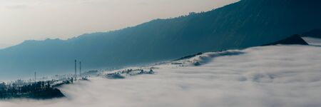 murk: The mountains and the fog hallowing the mountain side of volcano Bromo on Java in Indonesia