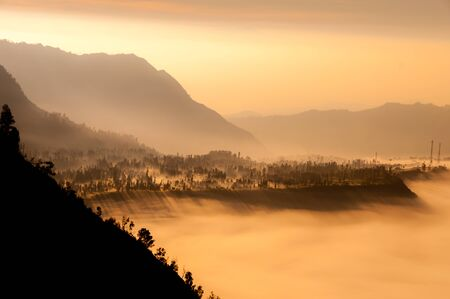 Steep black mountain silhouette in front of thick Fog and mist of volcano Bromo in Indonesia