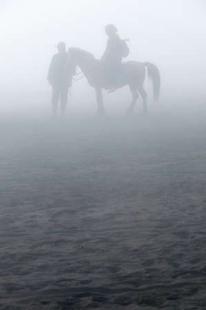 murk: Silhouette of people and horses in fog and mist of sulphur volcano Bromo Stock Photo