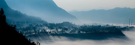 murk: Steep black mountain silhouette in front of thick Fog and mist of volcano Bromo in Indonesia