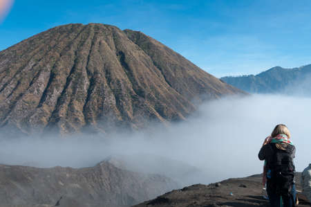 murk: Woman taking a picture of the Mountain with fog and mist at volcano Bromo