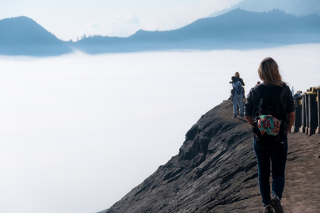 murk: Woman walking along top of volcano next to fog and mist of the sulphur volcano Bromo Stock Photo