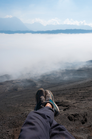 murk: Feet with shoes in front of Sheet of Fog smoke or Mist at Volcano Bromo in Indonesia