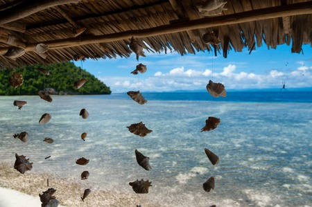 papua new guinea: Shells hanging from bamboo roof in front of the blue ocean and white sand beach in Raja Ampat, Papua New Guinea, Indonesia