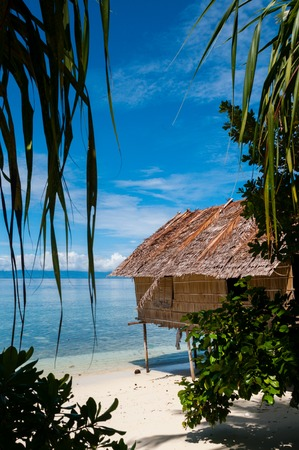 mountain hut: Nipa Hut on stilts at a Beautiful white sand beach Beach in front of the ocean in Raja Ampat, Papua New Guinea Stock Photo