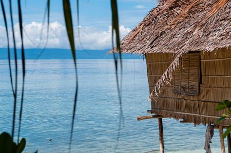 Nuova Guinea: Nipa capanna su palafitte in una bellissima spiaggia spiaggia di fronte all'oceano, a Raja Ampat, Papua Nuova Guinea, Indonesia Archivio Fotografico