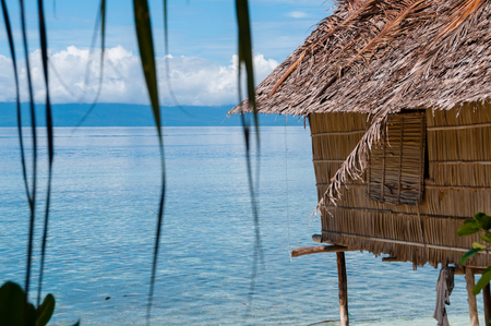 Nipa Hut on stilts at a Beautiful beach Beach in front of the ocean, in Raja Ampat, Papua New Guinea, Indonesia
