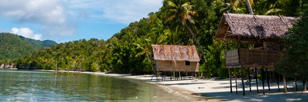 Nuova Guinea: Nipa capanne di bamb� in spiaggia di sabbia bianca con le palme a Raja Ampat, Papua Nuova Guinea, Indonesia