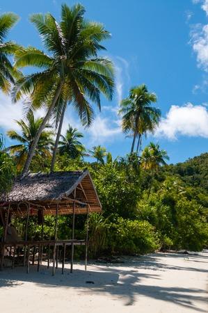 new guinea: Nipa capanna su palafitte in una bellissima spiaggia di sabbia bianca spiaggia di fronte all'oceano a Raja Ampat, Papua Nuova Guinea Archivio Fotografico