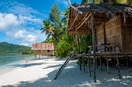 Nuova Guinea: Nipa capanne di bambù in spiaggia di sabbia bianca con le palme a Raja Ampat, Papua Nuova Guinea, Indonesia