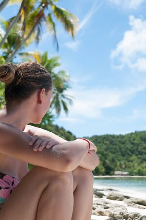 papua new guinea: Sitting Woman by the beach looking at the vast ocean at beach in Raja Ampat, Papua New Guinea, Indonesia Stock Photo