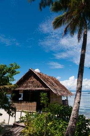new guinea: Nipa Hut on stilts at a Beautiful beach Beach in front of the ocean, in Raja Ampat, Papua New Guinea, Indonesia