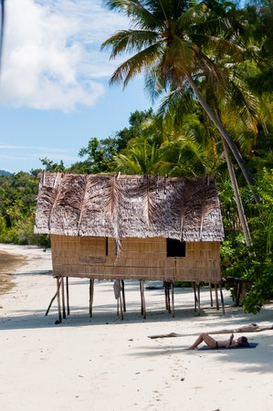 papua new guinea: Lonely Nipa Hut on stilts with palm trees at a Beautiful beach  in front of the ocean and person Sunbathing in Raja Ampat, Papua New Guinea, Indonesia
