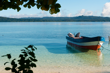 Small wooden boat in shallow clear water tied up by the white sand beach in Raja Ampat, Papua New Guinea Foto de archivo