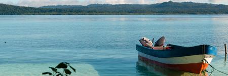 Nuova Guinea: Piccola barca di legno in acqua pulita poco profonde legato dalla spiaggia di sabbia bianca di Raja Ampat, Papua Nuova Guinea Archivio Fotografico