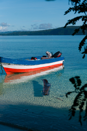 papua new guinea: Small wooden boat in shallow clear water tied up by the white sand beach in Raja Ampat, Papua New Guinea Stock Photo