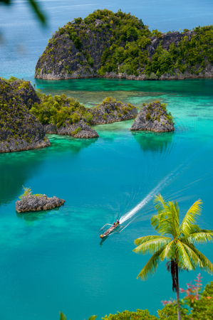 Boat Cruising Around small green Islands belonging to Fam Island in the sea of Raja Ampat, Papua New Guinea, Indonesia