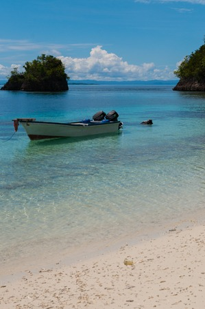 new guinea: Piccola barca di legno in acqua pulita poco profonde legato dalla spiaggia di sabbia bianca di Raja Ampat, Papua Nuova Guinea Archivio Fotografico