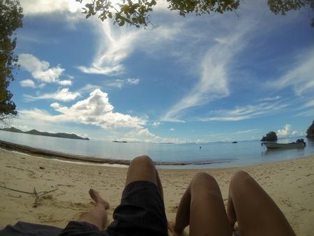 new guinea: Piedi di due persone che pongono sulla spiaggia di sabbia sotto il cielo blu rilassante a Raja Ampat, Papua Nuova Guinea, Indonesia