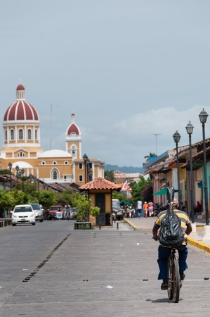 middle america: Man riding bike on street in city Granada, Nicaragua, Central America Stock Photo